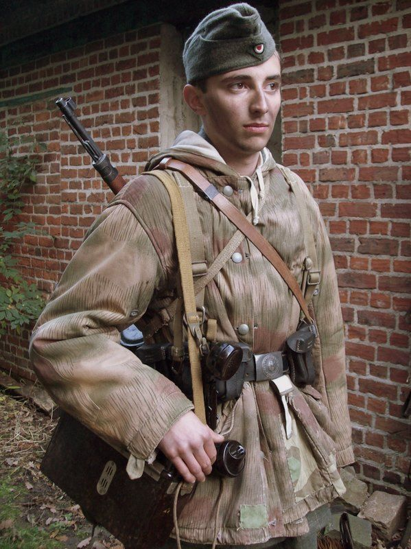 Volksgrenadier wearing a reversible sumpftarn camouflage smock and carrying a field telephone.