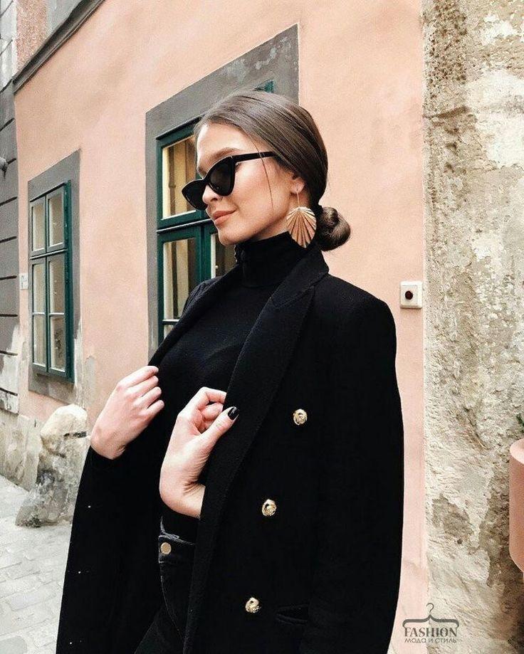 Schwarzer Rollkragenpullover, schwarzer Mantel, Sonnenbrille, Ohrringe