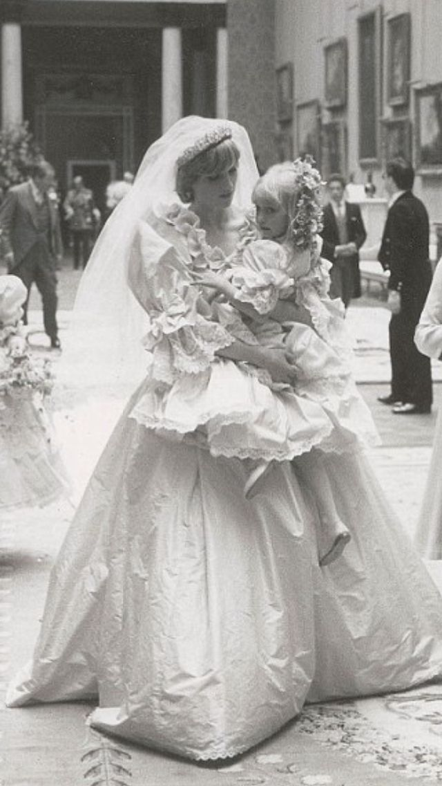 Whispering words of encouragement to her five-year-old bridesmaid, Diana, Princess of Wales, looks resplendent in her wedding dress as she carries the young girl through the grand rooms of Buckingham Palace. At her side is Queen, who just moments earlier had become her mother-in-law when she married Charles, the Prince of Wales, in a ceremony held at St Paul's Cathedral. The scene, striking in its intimacy and candidness.