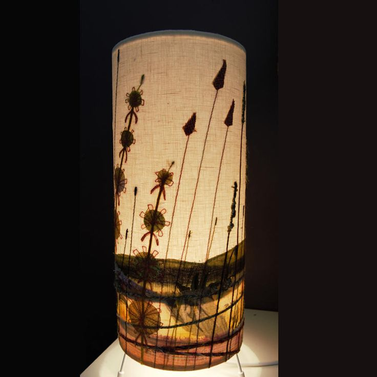 A beautiful lamp to sit on your table or shelf. I have stitched this using my unique style of appliqué and free-motion embroidery, inspired by the wonderful colours of the British landscape. It produces a lovely glow when illuminated.The lampshade has a fitted in-line switch on the cable and measures 15cm (diameter) by 38cm. Please use maximum 40 watt bulb (bayonet cap). Cable length 2 metres.