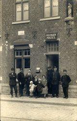 Het postkantoor in de Vrouwstraat. Op de foto herkennen we van links naar rechts: C. Arnoudt, F. Maertens, Van Dormael, J. Deserrano en Ethel Coats met hun kinderen Alex en Gabrielle, A. Deleu, E. Ducatelle en Jean Vankemmel.