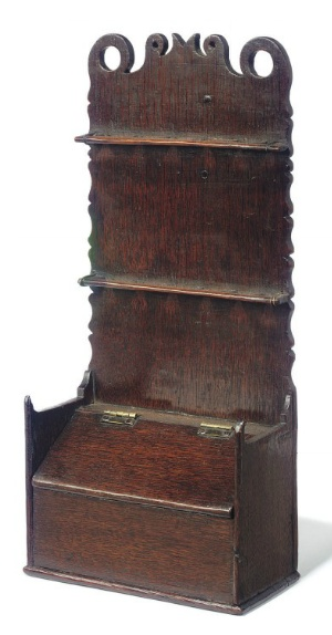 A GEORGE III OAK SPOON RACK   CIRCA 1780   With shaped back and hinged candle drawer below   15.12 in. (39 cm.) high