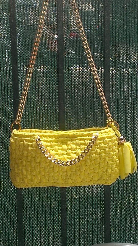 Pochette in lycra gialla con decorazioni in catena. Foderata con chiusura a magnete. Prezzo 45€