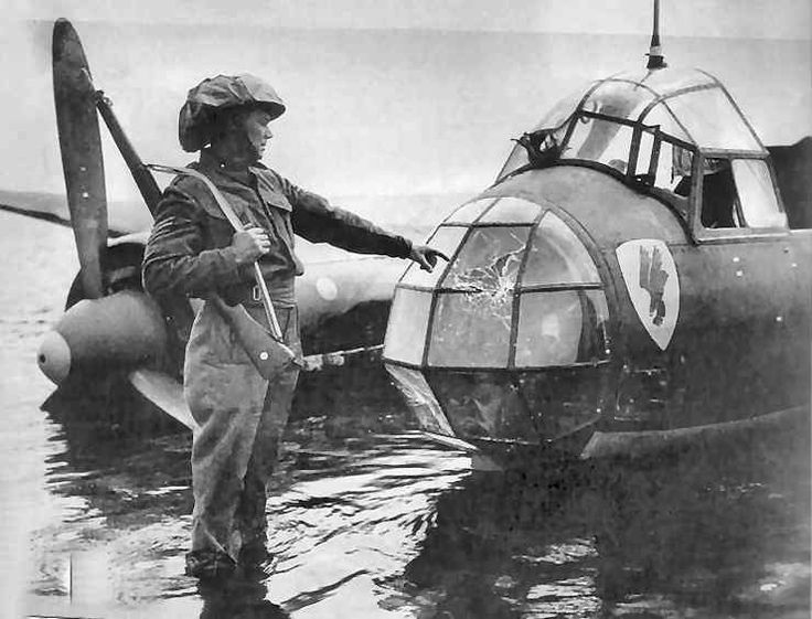 """Ju88A-1 4D+AD of Stab 3/KG30 was captured in a series of portraits by photographer Frank Lalouette of Bognor Regis starting with a soldier pointing out strikes in the nose glazing. On being engaged by No 602 Squadron RAF on 9 September 1940, the bomber ditched on the foreshore at Pagham Harbour, claimed by S/L Alexander VR """"Sandy"""" Johnstone and P/O Archibald """"Pat"""" Lyall 20m north of Mayfield at 17.40, following a final attack by F/O Paul C Webb."""