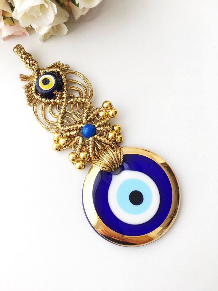 A personal favourite from my Etsy shop https://www.etsy.com/listing/514783968/blue-evil-eye-wall-hanging-gold-macrame Blue evil eye wall hanging | gold macrame evil eye | gold evil eye charm | evil eye decor | nazar boncuk wall hanging | turkish evil eye  evil eye size: 7cm x 7cm Length:14cm Evil Eye is associated with the eyes and looking from these eyes throughout the history. According to evil eye superstition, negative thoughts and glares comes out of eyes #evileye #evileyewallhanging