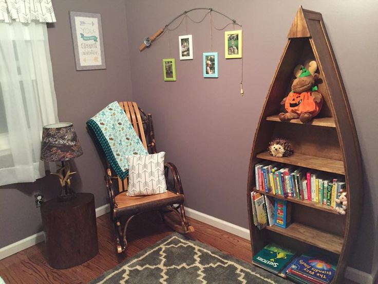 Camping / Outdoors themed Nursery for a baby boy ! Boat bookshelf, amish rocking chair made of rustic tree branches, deer antler lamp, arrow pattern pillow and curtain, you are our greatest adventure sign, tree stump side table, and a fishing pole picture frame holder!