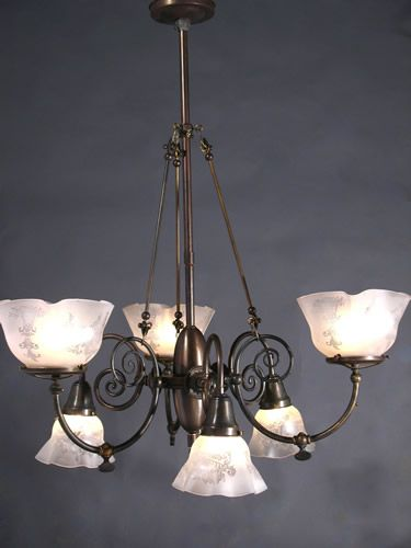 Circa 1895 this pair of antique gas and electric chandeliers are festooned with serpentine detail