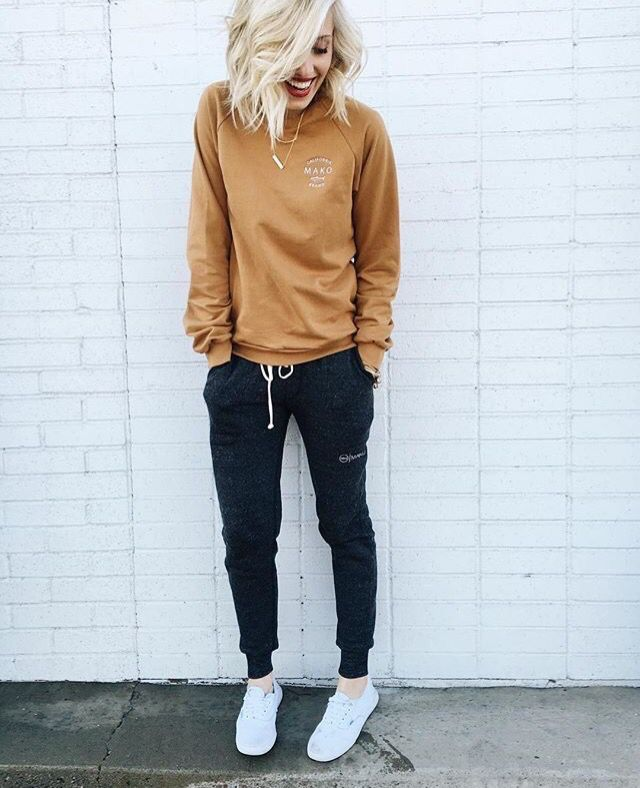 muted yellow-orange sweater with black joggers and white sneakers