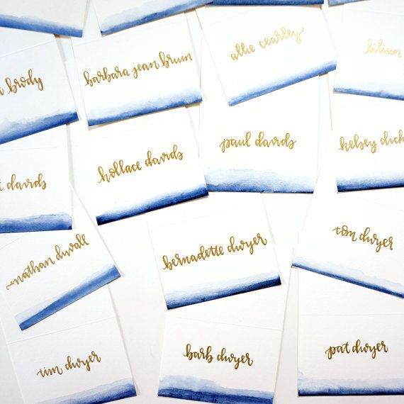watercolor ombré handwritten escort cards -- bottom edge is hand-painted in navy watercolor and calligraphy is handwritten in gold metallic ink -- unique and artistic touch for wedding reception decor!