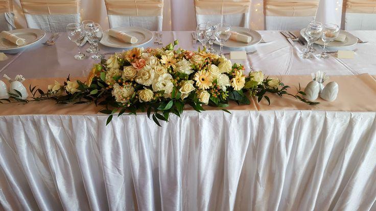 Krém és barack főasztaldísz szegfűvel, gerberával, rózsával és egy kis zölddel. Nézd meg további referenciáinkat és kérd egyéni ajánlatunkat a saját esküvőd álomdekorációjára: http://eskuvoidekor.com/viragdekoracio