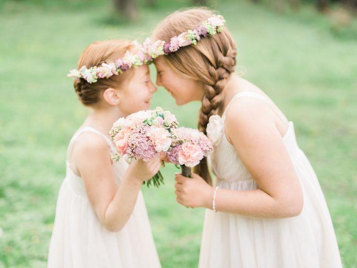 De söta brudnäbbarna har små buketter i händerna och blomsterkransar på huvudet i bröllopets härliga pastellfärger