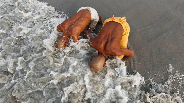 3.jan.2014 - Peregrinos hindus mergulham noo rio Ganges e a Baía de Bengala, ato que eles consideram ser ...