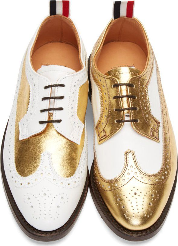 "Name: White and Gold Metallic Leather Longwing Brogues • Designer: Thom Browne • Description: ""Low-top longwing brogue shoes in white matte and gold metallic leather. Almond toe. Classic perforation design throughout quarter and eyerow. Buffed white leather panel at heel counter. Signature red, white, and blue striped grosgrain pull-tab at collar. Stacked leather sole in dark brown."" — ""Thom Browne: White and Gold Metallic Leather Longwing Brogues"", Ssense (Retrieved: 27 November, 2014)"