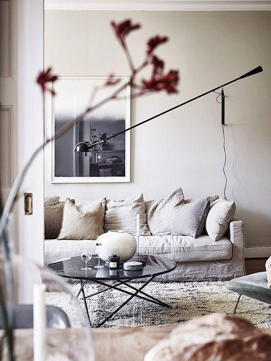 inspiring wabi sabi home decor via Entrance Realtors | minimal monotone scandinavian decor | round marble coffee table | relaxed linen sofa | Make it your own with an IKEA Karlstad sofa with a Bemz Loose Fit Urban cover