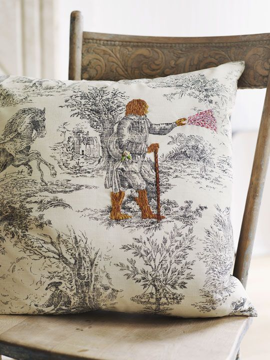 Vintage toile pillow embroidered with a magical creature by textile artist, Richard Saja.