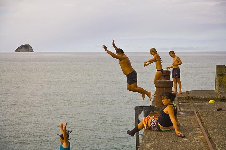 Kids jump from the the longest wharf in the southern hemisphere at Tolaga Bay. Efforts are being made to preserve the decaying wharf, see more at New Zealand Journeys app for iPad www.gopix.co.nz