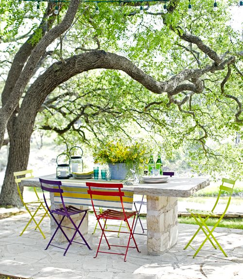 On this Texas ranch, metal folding chairs (from Barton Springs Nursery in Austin) offer colorful contrast to a table built out of Texas limestone.   - HouseBeautiful.com
