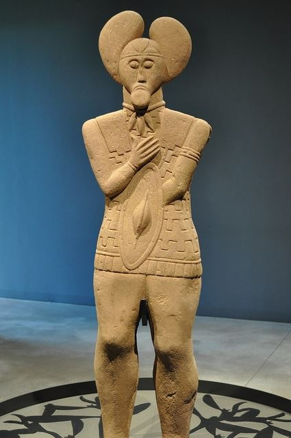 The Glauberg site near Hesse, Germany is an ancient Celtic Oppidum (town/social centre) and contains a monumental burial mound dating to around 500 BC. This statue depicts a Celtic warrior complete with tunic and trousers; he is also equipped with a sword and shield which suggest seniority. The sculpture is believed to be an accurate likeness of the interred prince, as the figure is decorated in jewelry excavated from the burial mound itself. Note the three-pronged Torc around the Prince's…