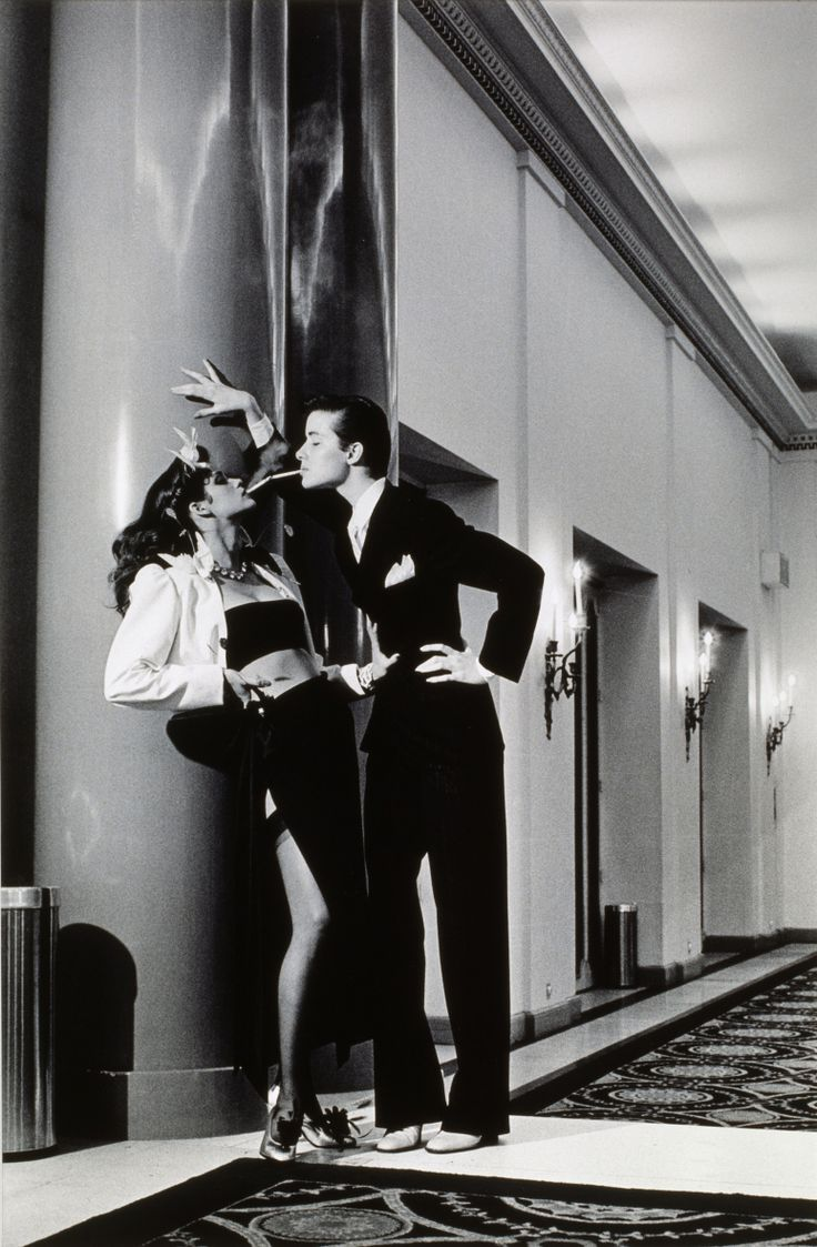 ..Helmut Newton, Yves Saint Laurent – Woman into Man, lighting a cigarette, Vogue, 1979..