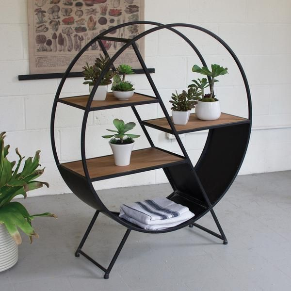 """Staggered shelves within a round frame set the stage for creative displaying. The black iron nicely contrasts with the rich natural wood finish.    Metal & Wood Construction  Accessories not included  Dimensions: 36""""W x 11""""D x 42""""H  Assembly Required"""