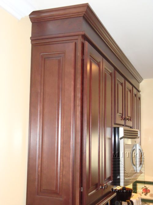 Kitchen bulkheads don't HAVE to be ugly! Cover in plywood or veneer and add thick matching crown molding.