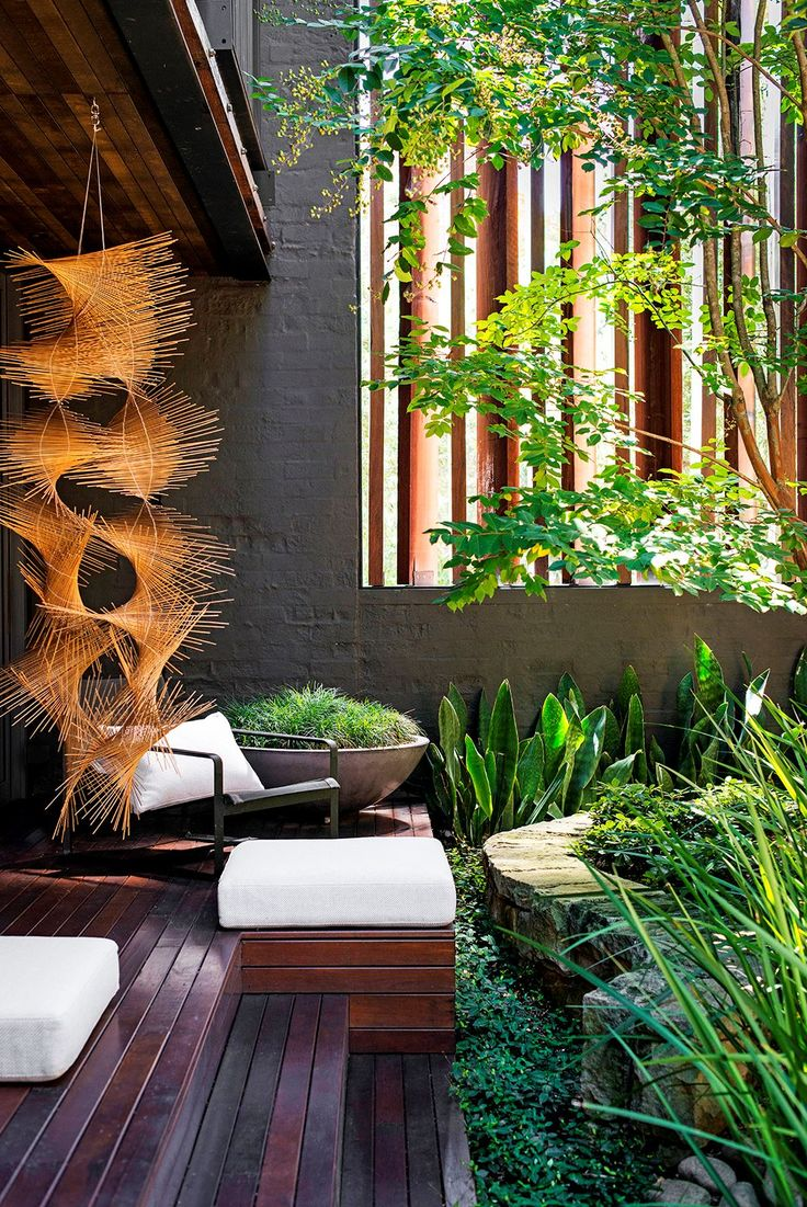 Industrial-style urban courtyard:A hanging reed sculpture by Tracey Deep enlivens the atrium. To soften the sandstone wall that snakes through the space, Richard has planted a variety of foliage plants including strappy wild iris, mounds of Pittosporum 'Miss Muffet' and long-leafed *Sansevieria* 'Congo'. The groundcover is *Trachelospermum asiaticum* (Japanese star jasmine) and the concrete bowl is planted with mondo grass.