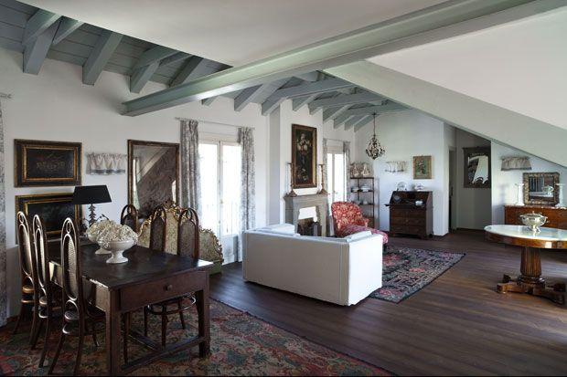 Il soggiorno dell'appartamento nel sottotetto, con le TRAVI in legno che sostengono  la copertura dipinte di bianco: è quasi completamente arredato con pezzi Ottocento