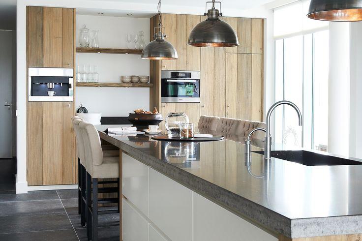 De combinatie van houten elementen en strak lakwerk maken een prachtig geheel van deze tijdloze keuken.