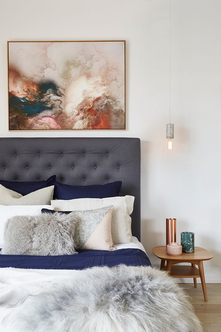 Grey upholstered bed with moody artwork hanging above. The dark blue and grey bedding is divine.