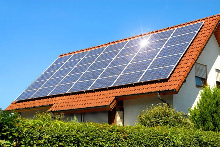 Panel słoneczny na dachu czerwony odzwierciedlających słońca i chmurki niebieski