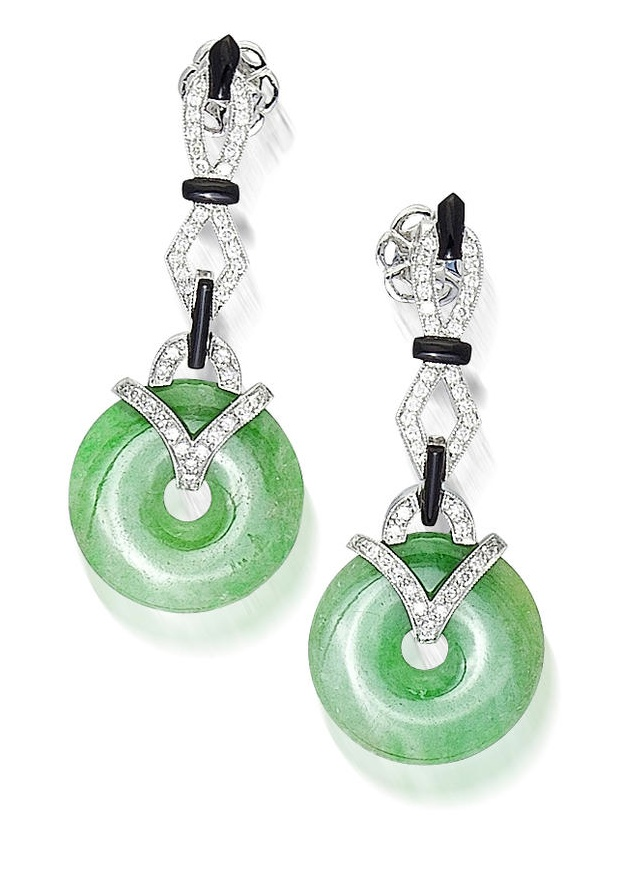 A pair of jadeite jade, diamond and onyx pendant earrings, Eli Frei  each designed as a circular jade bi suspended from a geometric diamond line accentuated with onyx; signed Frei; estimated total diamond weight: 1.00 carat; mounted in eighteen karat white gold; length: 1 7/8in.