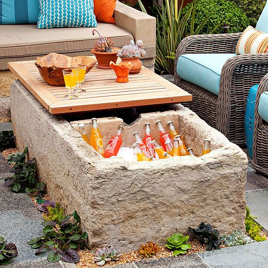 Carved into a massive limestone block and capped with a removable teak lid, this rugged outdoor coffee table hides a delightful surprise inside: a drink cooler!