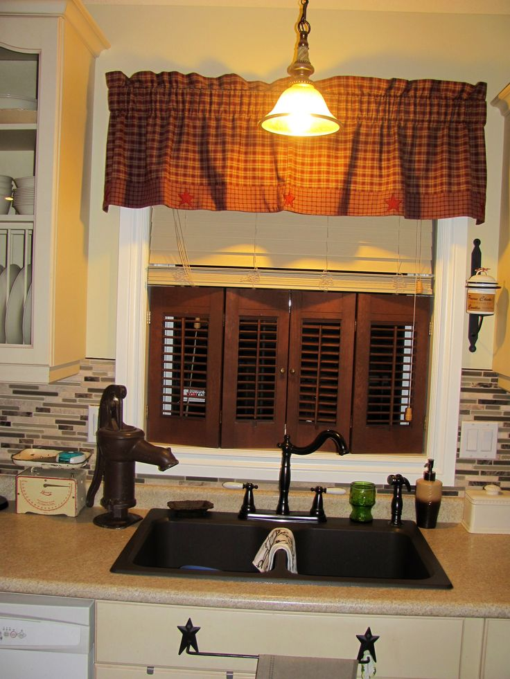 Wooden shutters, plaid valance, and antique cast iron pump, gives a nice country feel to the kitchen.