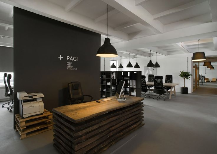 Located in a former factory, the office for advertising agency Pride Interactive also features glazed meeting rooms with wooden frames and plank and batten doors.