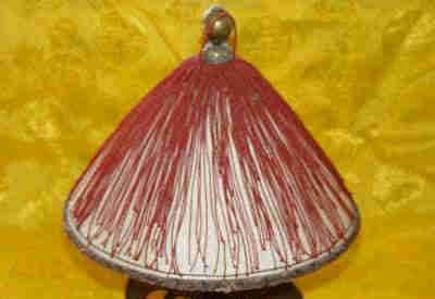 The official hat of the Qing Dynasty was topped with a knob made of a gem or silver and gold ornament, which indicated the wearer's rank and power. A ruby knob represented a first-rank official. The most common knobs were rosy red, or bright red, while the most precious were bloody red.  A coral knob signified a 2nd-rank official. The coral was hard and red in most cases, with the bright red ones being the most precious.