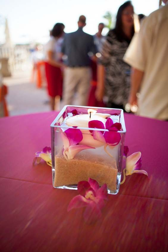 The perfect beach wedding centerpiece: floating candles with sand in the bottom and flower petals on top