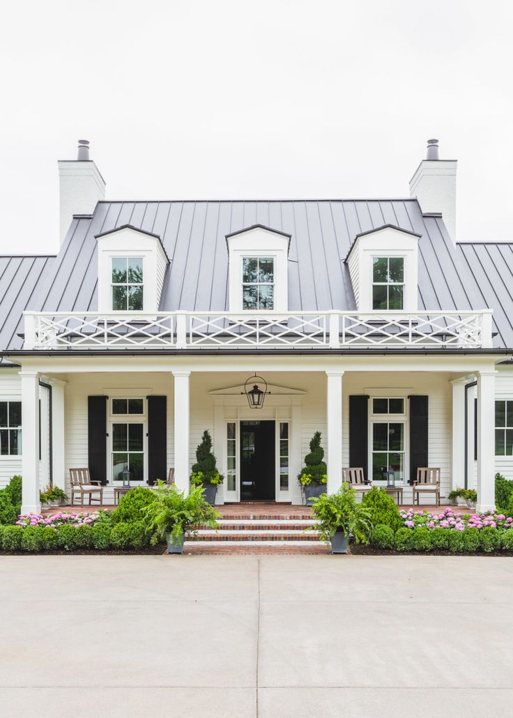 The front porch is symmetrically anchored by two pairs of planters, hedges and flowers. Image credit: Alyssa Rosenheck