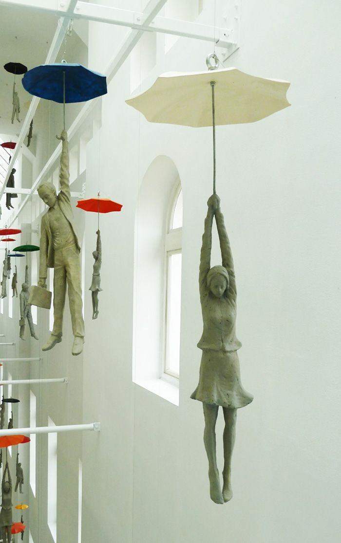 """In his installation """"Slight Uncertainty,"""" Artist Michal Trpák puts a philosophical spin on the Mary Poppins flight by umbrella. The piece features many cement figures hanging dearly onto open umbrellas in a rainbow's spectrum of colors, all of the individuals floating in an atrium-type space in the EBC office center in Prague. Uncertainty rests in …"""