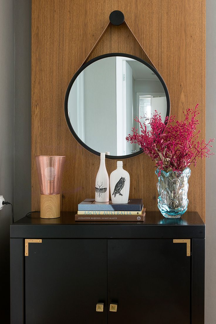 Apartamento moderno, decoração do hall de entrada com espelho redondo, flores e móvel preto.