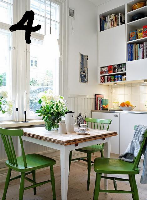 Gröna pinnstolar piggar upp i ett vitt kök med släta luckor.