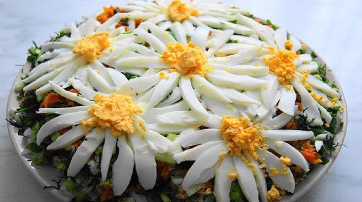 """Salata aspectuoasă """"Flori de mușățel"""" se prepară din ingrediente accesibile, dar rezultatul este delicios. Aspectul său deosebit cu romanițe întotdeauna îți ridică dispoziția și provoacă bucurie și emoții pozitive. INGREDIENTE: -½ pahar de orez cu bob lung; -2 piepturi de pui; -2 morcovi; -2 castraveți; -1 ceapă; -3 ouă; -maioneză; -frunze de salată; -mărar. MOD DE PREPARARE: 1.Fierbeți orezul în apă cu sare. 2.Dați morcovul prin răzătoare și prăjiți-l în ulei. 3.Fierbeți ouăle și pieptul de…"""