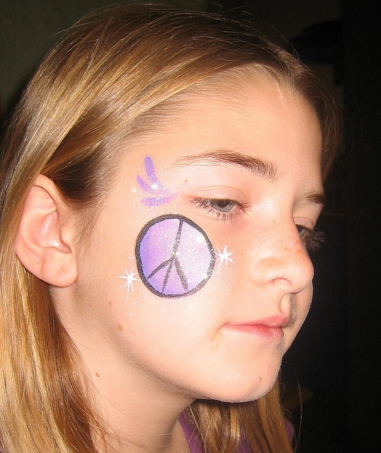face painting (I use acrylic paint) and body shimmer glitter.  Could paint a flower or peace sign