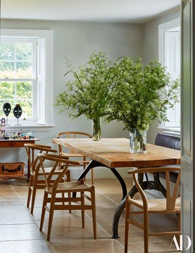 Hand Wegner chairs from the Conran shop flank a custom-made barrjoinery table in the kitchen; Pablo Picasso owned one of the dan masks | archdigest.com
