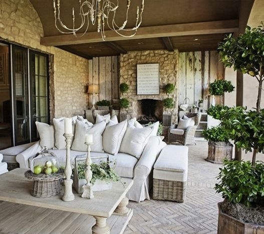 neutral outdoor patio--I like the infusion of green plants, and the spindly chandelier.