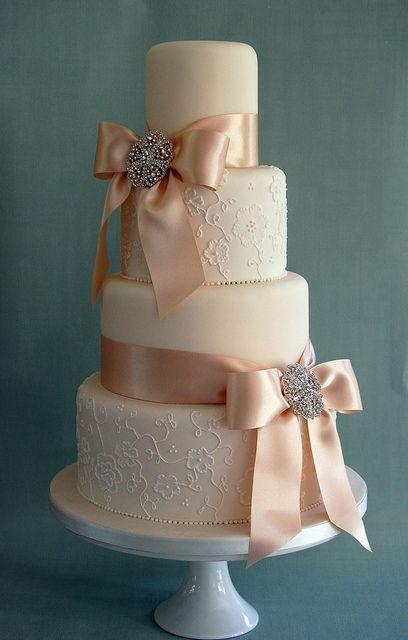 Bolo de casamento com textura de renda e laços de cetim.
