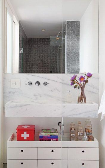 Dois banheiros viraram um só, fechado por portas de correr de vidro jateado (veja o reflexo no espelho), que deixam passar a luz, pois no ambiente não há janelas. 15. Como a bancada é pequena, o arquiteto aproveitou o espaço embaixo dela para colocar um gaveteiro laqueado de branco que serve também para ordenar os objetos do morador. O tampo é uma bandeja espelhada.