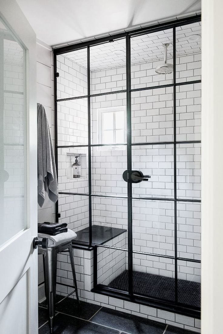 A steel framed shower door with small glass panels adds a classic touch to a more modern black and white bathroom full of subway tiles and personality.