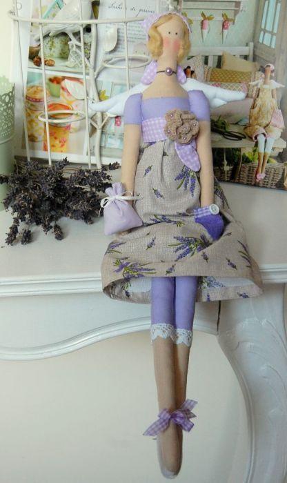 Lalka tilda wykonana z bawełnianych tkanin, utrzymana w lawendowej kolorystyce. Zdobiona uroczymi dodatkami: koronka, koraliki, kokardki, woreczek, kieszonka filcowa, chusta na włosach. Włosy wykonane z włóczki czesankowej, wypełnienie silikonowe. Wysokość lalki - 50 cm.