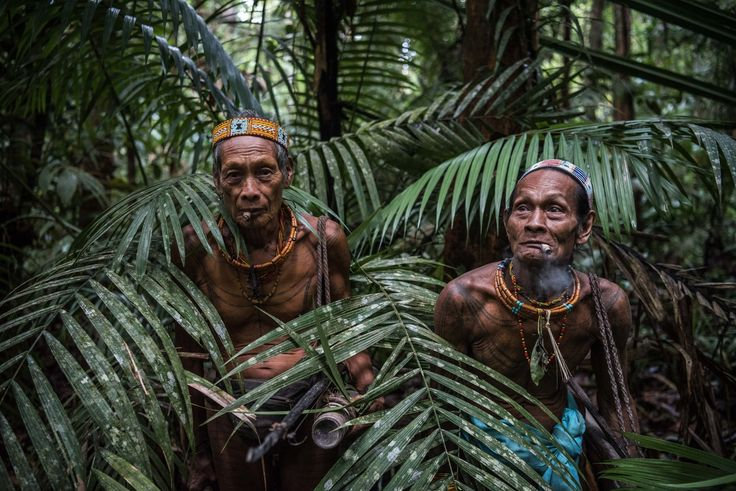 Teu Kapik Sibajak, left, and Aman Aqwi Sakkukuret, members of the Mentawai tribe, on the island of Siberut in Indonesia. Credit Sergey Ponomarev for The New York Times
