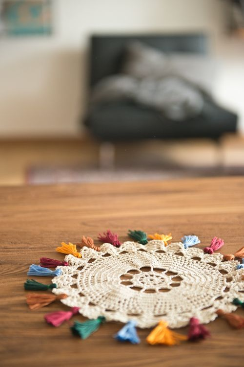 Embroidery floss tassels on a crocheted doily, so pretty.